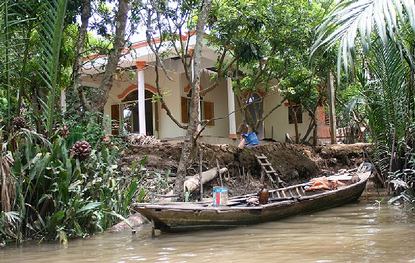 house with boat up the mekong river
